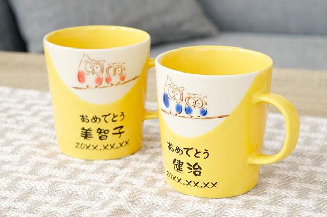 ふくろうが寄り添う黄色いマグカップ
