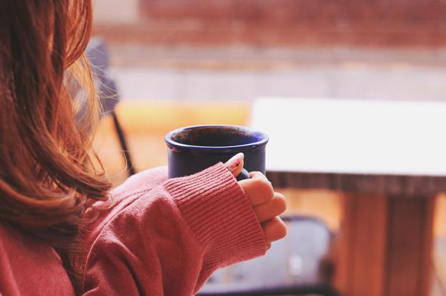 マグカップに入った温かいコーヒーを飲む女の子
